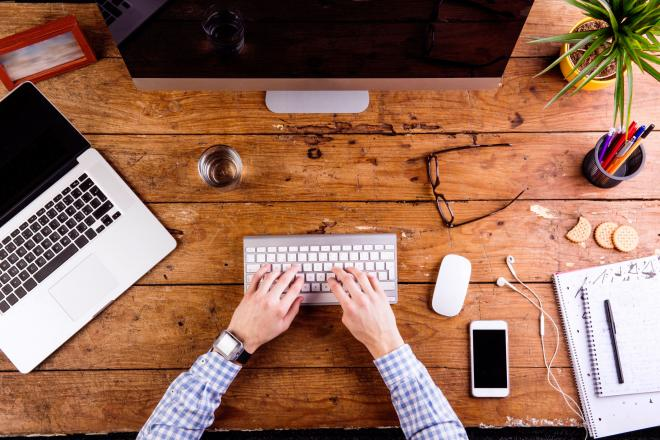 graphicstock-business-person-working-at-office-desk-writing-on-computer-keyboard-smart-watch-on-hand-and-smart-phone-on-the-table-glass-of-water-notepad-and-eyeglasses-and-various-office-supplies-around-the-workplace-flat-lay_HOjlaSSz-  (1).jpg